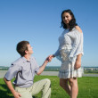 Boyfriend proposing to girlfriend - Stock Photo