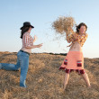 Girls play with hay — Stock Photo