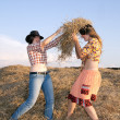 Happy girls play with hay — Stock Photo
