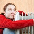 Stock Photo: Girl is sitting near oil heater