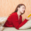 Pretty young girl reading book on sofa — Stock fotografie