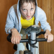 Weariness girl on exercycle — Stock Photo