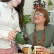Girl and women drink tea in the kitchen — Stock Photo