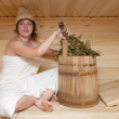 Young brunette woman sitting in sauna — Stock Photo