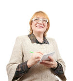 Senior woman writing on a notebook — Stock Photo