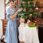 Girl decorating Christmas tree — Stock Photo