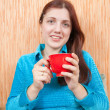 Girl relaxing with a red cup at home — Stok fotoğraf