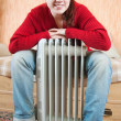 Stock Photo: Girl is sitting by oil heater