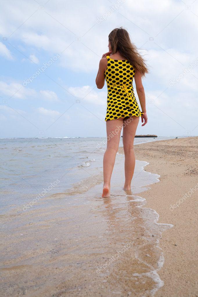 Дети девушка вид сзади на пляже, глядя на закат