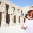 Girl is photographing an ancient statues - Stock Photo