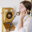 Girl is speaking by retro wooden phone — Stock Photo