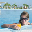 Girl in tropical pool with orange juice — Stock Photo