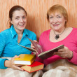 Two happy women reading a book on sofa — Stockfoto