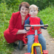 Grandmother with boy on tricycle — Stock Photo