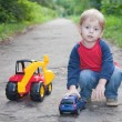 Child playing toy car in park — Stock Photo