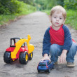 Stock Photo: Child playing toy car in park