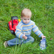 Boy playing toy truck in grass — 图库照片