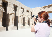 Girl is photographing an ancient statues — Stock Photo