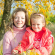 Mother with little girl in autumn park — Stok fotoğraf