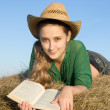 Girl reading at fresh hay — Stock Photo