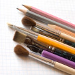 Pencils and brushes on copy-book — Stock Photo