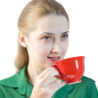 Girl drinks tea from a red cup — Stock Photo #2171629