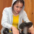 Stock Photo: Weariness girl on exercycle
