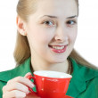 Girl drinks tea from a red cup — Stock Photo #2208977
