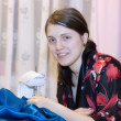 Smiling girl is sewing — Stockfoto