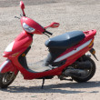 Stock Photo: Red new scooter on road from summer