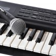 A microphone lying on the keys - Stock Photo