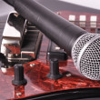 A microphone lying on a guitar - Stock Photo