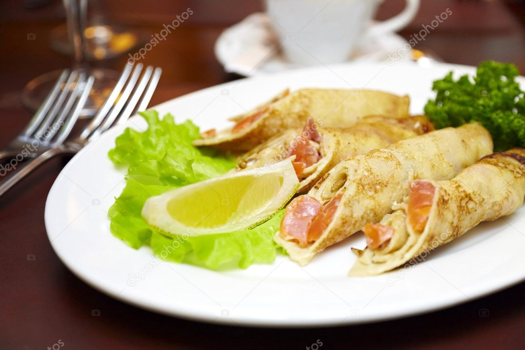 Pancakes with a salmon on a plate with a salad and lemon substrate  Stock Photo #2597425