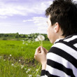 Teenager blowing dandelion — Stock Photo #1547969