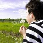 Teenager blowing dandelion — Stock Photo