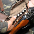 Hunter charges rifle ammunition - Stock Photo