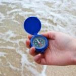 Dark blue compass in hands — Stock Photo
