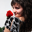 Beautiful young girl with a red rose - Stockfoto