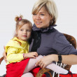 Stock Photo: Little girl on hands for a young mother in a wicker chair on the grey