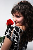 Beautiful young girl with a red rose — Stock Photo
