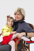 Little girl on hands for a young mother in a wicker chair on the grey — Stock Photo