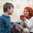 Son giving his illing mother tea — Stock Photo