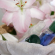 Toiletries in basket and pink lily - Stock Photo