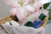 Toiletries in basket and pink lily — Stock Photo