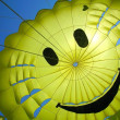 Yellow fun parachute with smiling person — Stock Photo