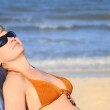 Woman in bikini lying on the beach smili — Stock Photo #1103630