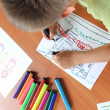 Caucasian boy drawing on paper - Stock Photo