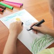 Child draws green grass and sun on paper — Stock Photo