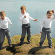 Three boys dance on green grass — 图库照片