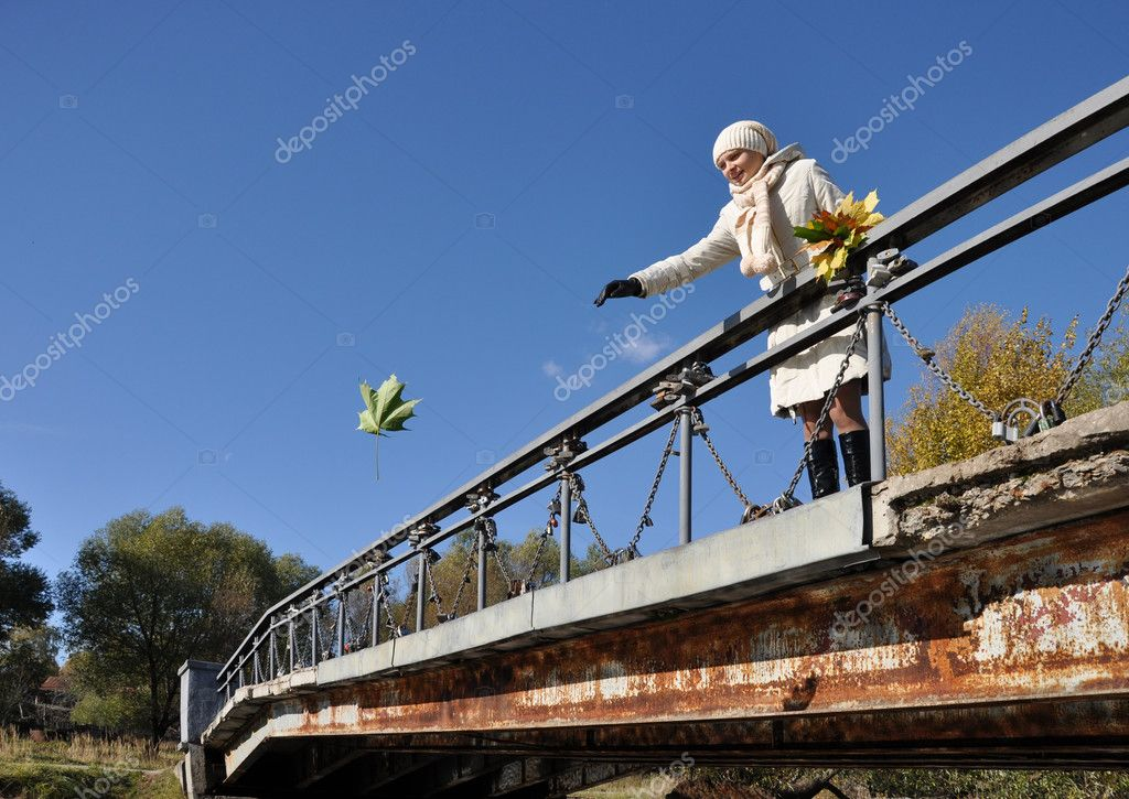 Girl on bridge thinks desire and throws maple leaf in water  Stock Photo #1104464